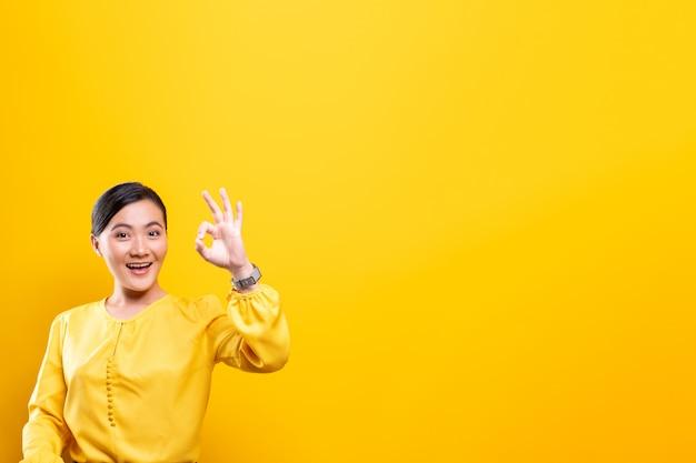 Mujer feliz que muestra gesto aceptable aislado en la pared