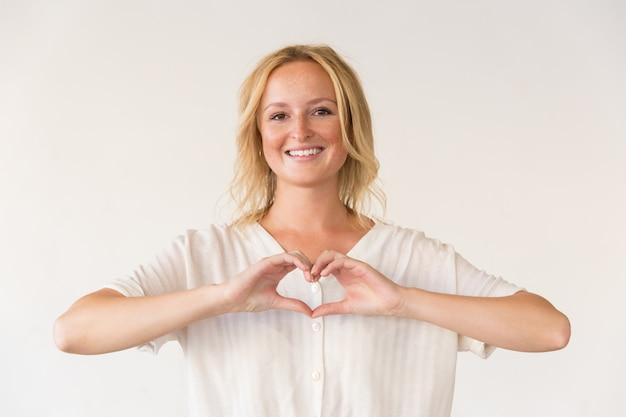 Mujer feliz que muestra gesto del corazón de la mano