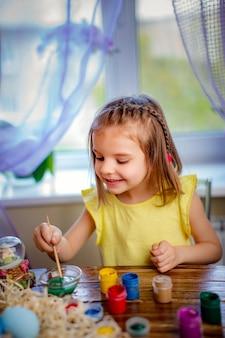 La mujer feliz que pinta los huevos de pascua, niño pequeño en casa se divierte. vacaciones de primavera