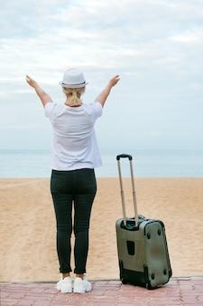 Mujer feliz que respira el aire fresco profundo y que levanta los brazos en la playa. mujer feliz de vacaciones.
