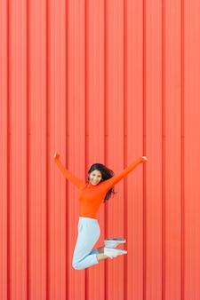 Mujer feliz que salta contra el fondo corrugado rojo mientras el brazo extendido