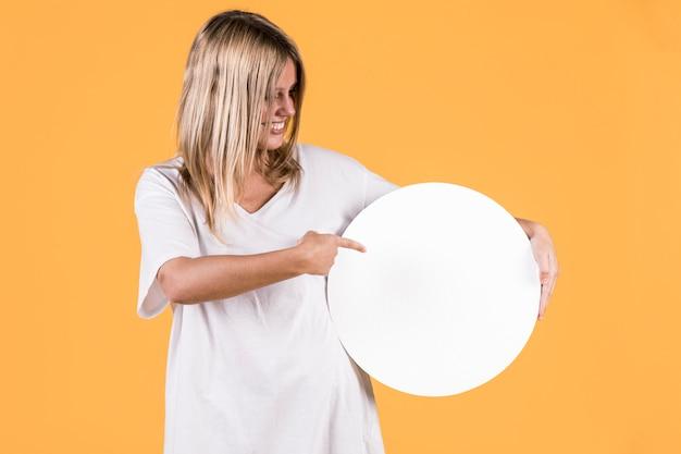 Mujer feliz que señala en el marco circular en blanco blanco sobre fondo amarillo