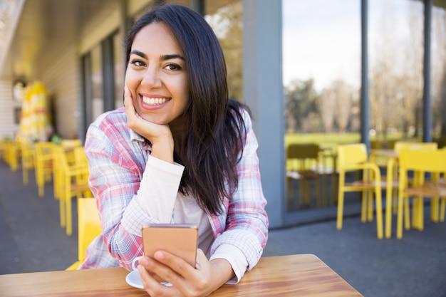 Mujer feliz que se sienta en café de la calle con smartphone y café