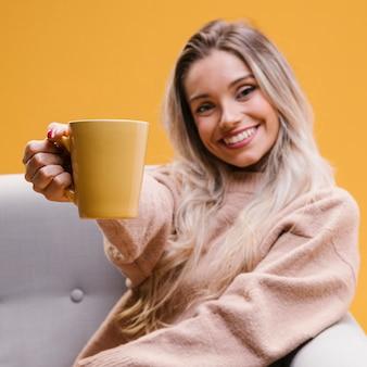 Mujer feliz que se sienta en el sofá que muestra la taza de café en casa