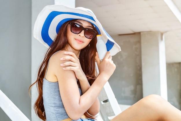 Mujer feliz que sonríe en las gafas de sol que sostienen el cosmético de empaquetado protector solar ultravioleta de la botella de la loción.
