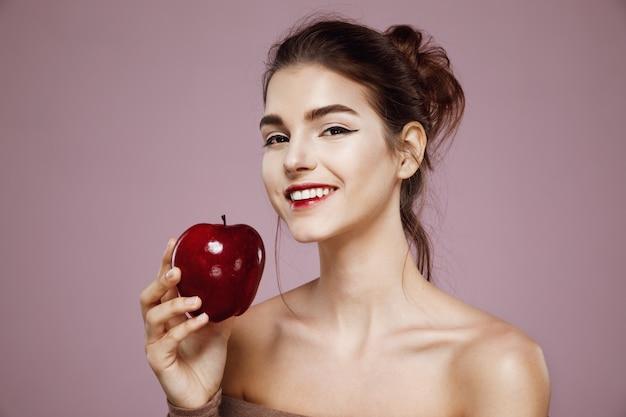 Mujer feliz que sonríe sosteniendo la manzana roja en rosa