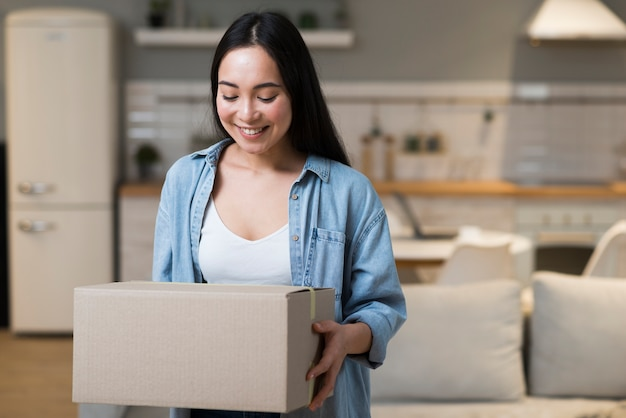 Mujer feliz que sostiene la caja con pedido en línea