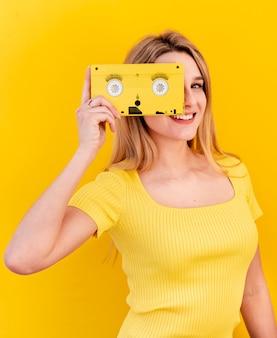 Mujer feliz que sostiene el cassette viejo