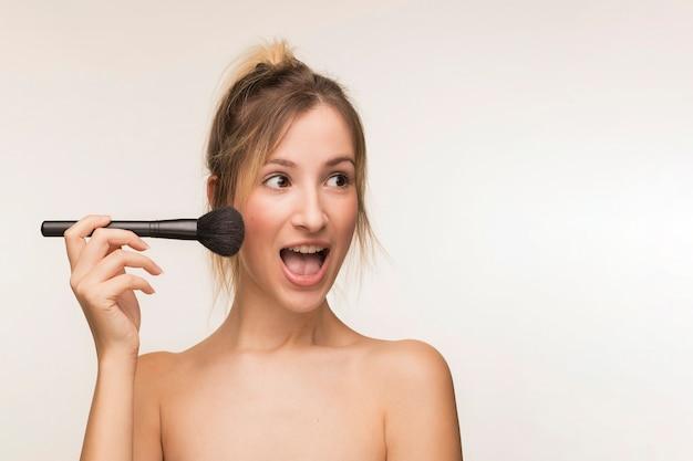 Mujer feliz que sostiene el cepillo del maquillaje