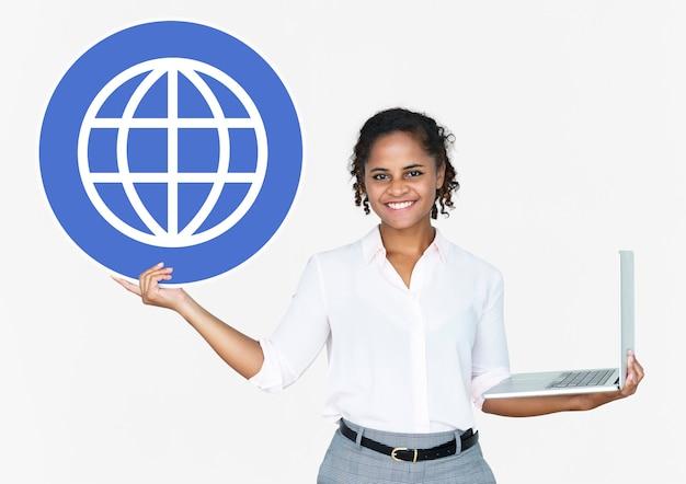 Mujer feliz que sostiene una computadora portátil y un icono de www
