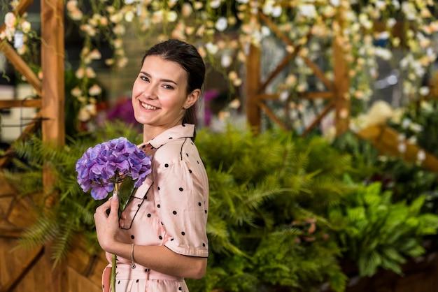 Mujer feliz que sostiene la flor azul en casa verde