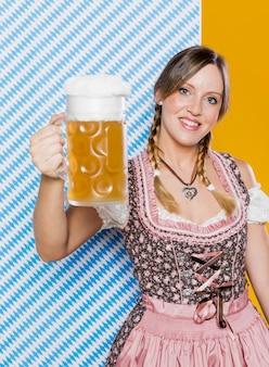 Mujer feliz que sostiene la jarra de cerveza