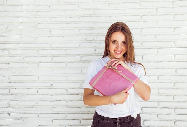 Mujer feliz que sostiene la caja de regalo rosada delante de la pared de ladrillo