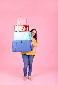 Mujer feliz que sostiene la pila de regalos coloridos contra el contexto rosado
