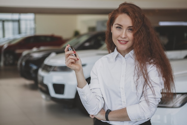 Mujer feliz que sostiene las llaves del coche a su automóvil nuevo