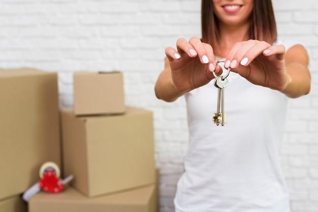 Mujer feliz que sostiene llaves