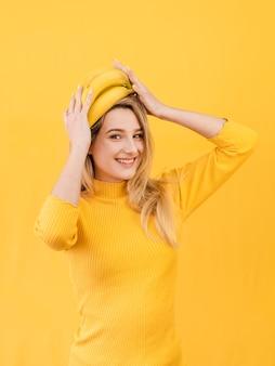 Mujer feliz que sostiene plátanos