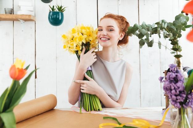 Mujer feliz que sostiene el ramo hermoso de flores amarillas mientras que trabaja