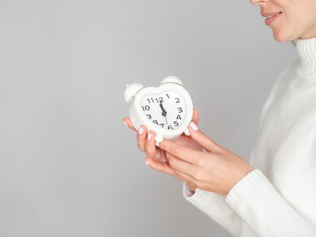 Mujer feliz que sostiene el reloj del corazón