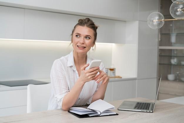 Mujer feliz que sostiene smartphone