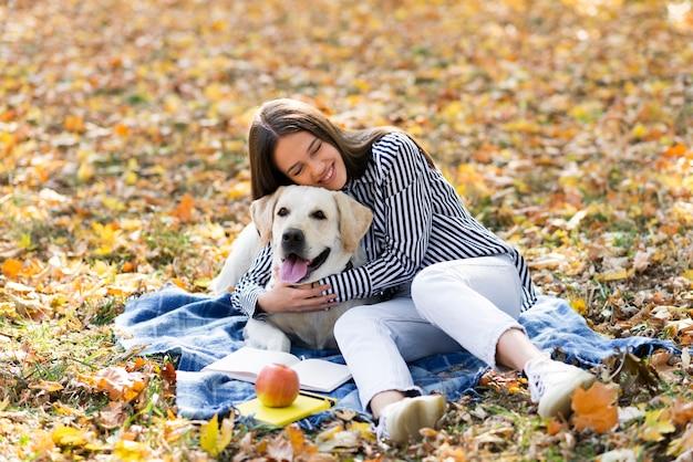 Mujer feliz que sostiene su perrito