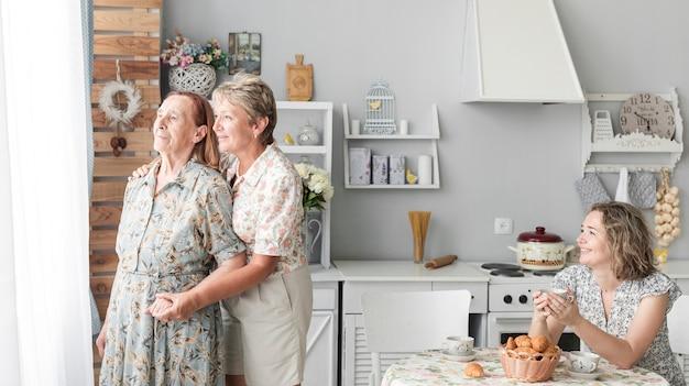 Mujer feliz que sostiene la taza de café que mira a su madre y magnífico