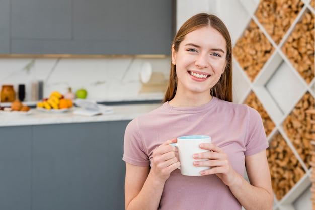 Mujer feliz que sostiene la taza en la cocina