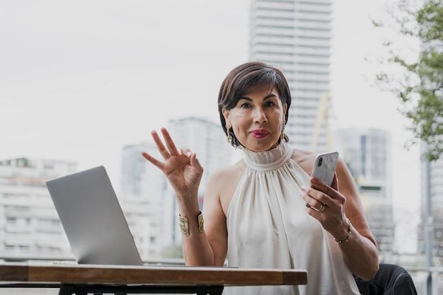 Mujer feliz que sostiene un teléfono en fondo urbano