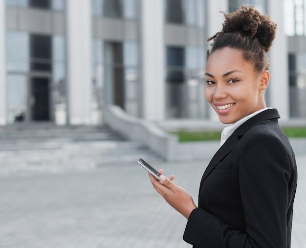 Mujer feliz que sostiene el teléfono