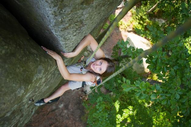 Mujer feliz que sube en una cuerda rocosa de la pared, bouldering