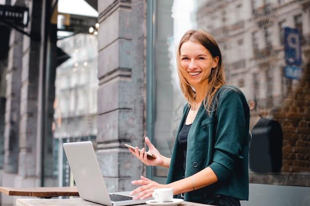 Mujer feliz que trabaja en una computadora portátil al aire libre
