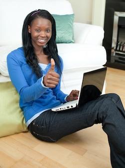 Mujer feliz que usa una computadora portátil que se sienta en el piso