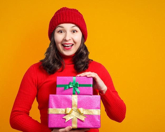 Mujer feliz con regalos de navidad en las manos. sobre una superficie amarilla.