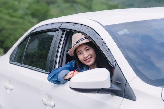 Mujer feliz relajada en las vacaciones del viaje del viaje por carretera del verano que miran la visión de la naturaleza hacia fuera ventana de coche