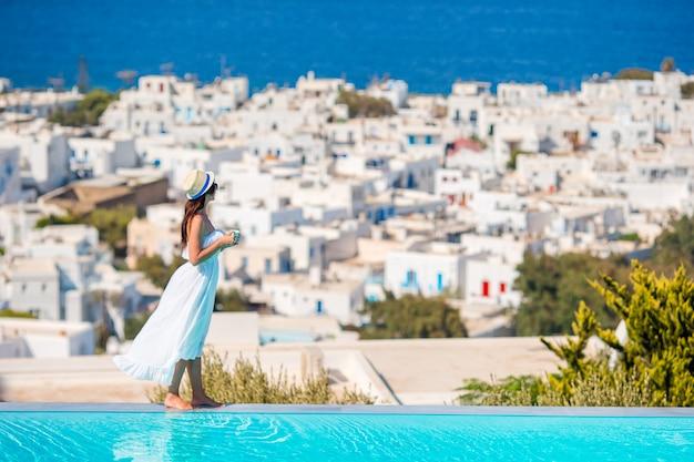Mujer feliz relajante en el borde de la piscina con impresionantes vistas de mykonos, grecia