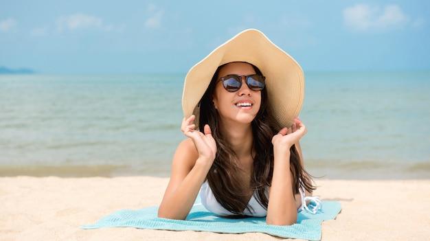 Mujer feliz relajante en la playa en verano