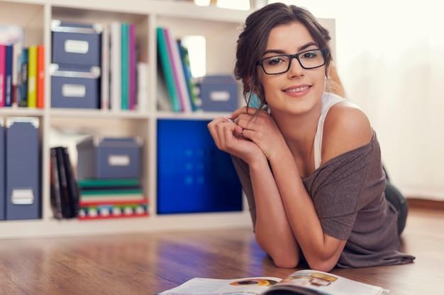 Mujer feliz relajante con revista en casa