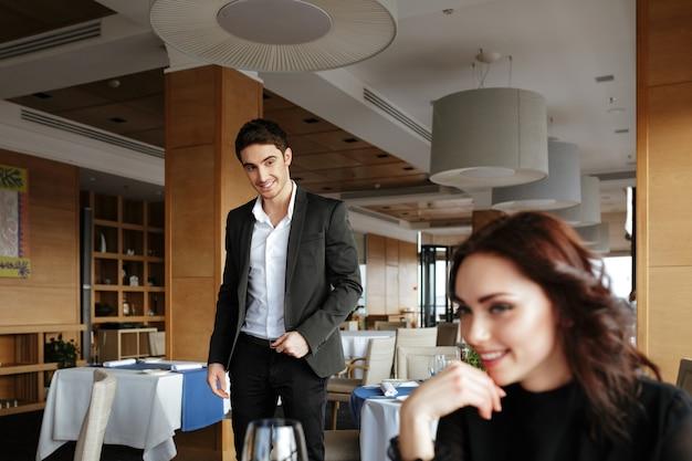 Mujer feliz en restaurante con hombre detrás de ella