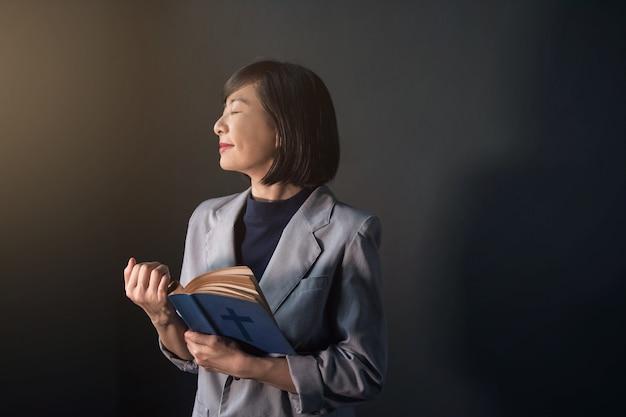 Mujer feliz rezando en la habitación oscura
