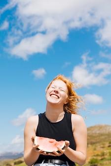 Mujer feliz con una rodaja de sandía