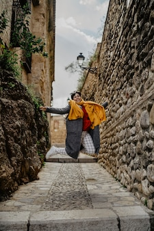 Mujer feliz en ropa de abrigo saltando en un callejón