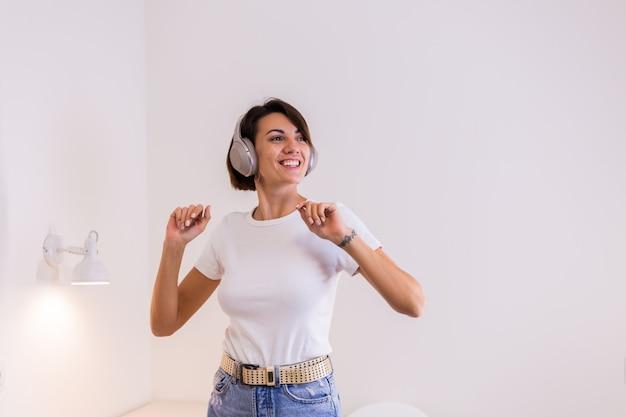 Mujer feliz en ropa casual en casa en el dormitorio escucha música en auriculares, bailando y saltando
