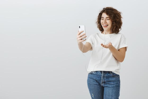 Mujer feliz saliente hablando por videollamada, mensaje de video con amigos mediante teléfono móvil y auriculares