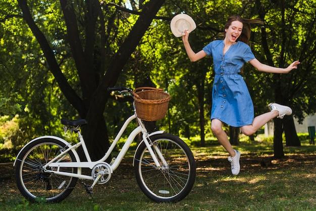 Mujer feliz saltando al lado de bicicleta