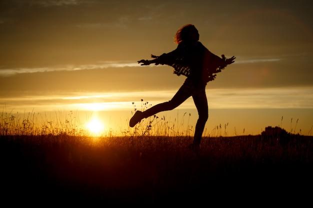 Mujer feliz saltando en el campo al atardecer