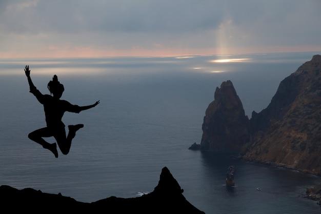 Mujer feliz saltando contra la hermosa puesta de sol. libertad, concepto de disfrute.