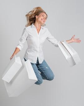 Mujer feliz saltando y posando mientras sostiene un montón de bolsas de la compra.