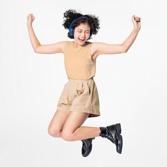Mujer feliz saltando usando audífonos bailando con música