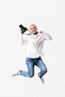Mujer feliz saltando y usando su cámara photo