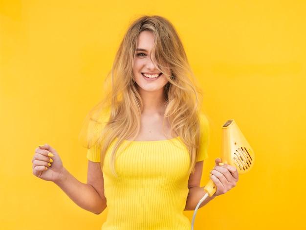 Mujer feliz secándose el pelo